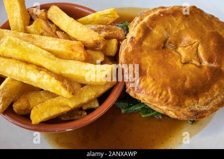 Copieux typique et savoureux repas au pub britannique: sex pâté à la viande en sauce servi avec un bol de golden fried chips chunky sur une plaque blanche chine Banque D'Images