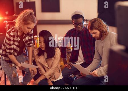 Groupe multi-ethnique de jeunes gens modernes écrit la musique ensemble tandis que les répétitions en studio d'enregistrement Banque D'Images
