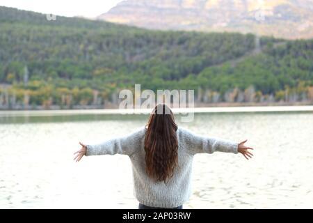 Vue arrière de happy woman celebrating holidays outstretching armes dans un lac