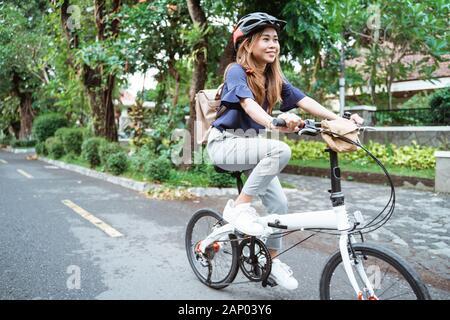 La jeune femme asiatique porte un casque et un sac qui monte sa bicyclette pliante Banque D'Images