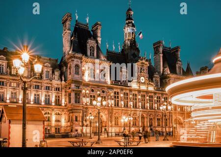 Hôtel de ville de Paris (Hôtel de Ville) au coucher du soleil avec carrousel tournant sur la place avant. Paris, France.