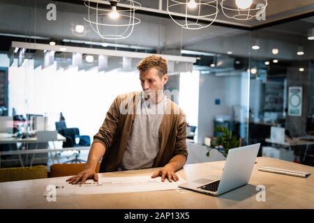 Portrait de l'architecte travaille avec le plan directeur de l'office