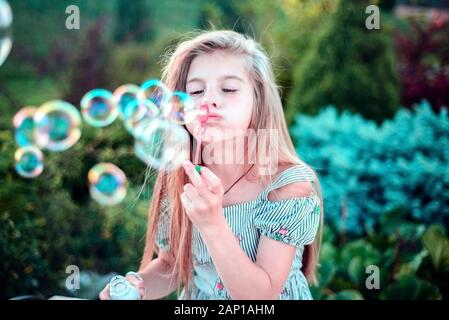 Portrait d'une belle petite fille soufflant des bulles de savon. Un enfant joue avec des bulles, sur un fond vert. Piscine Banque D'Images