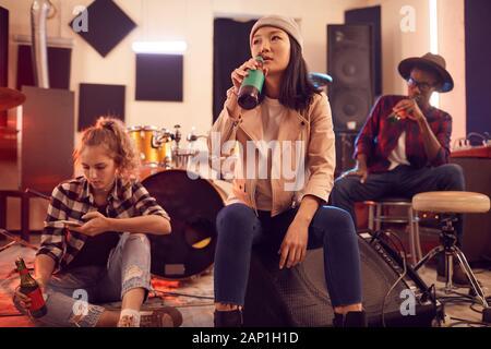 Groupe multi-ethnique des jeunes à se concentrer sur music studio boire jeune femme asiatique en premier plan de la betterave Banque D'Images