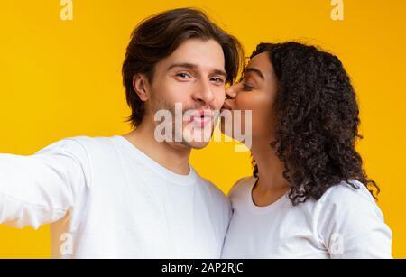 Loving Black copine s'embrasser son petit ami sur la joue alors qu'ils Prendre Des Selfies Banque D'Images