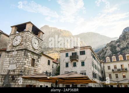 La lumière du soleil du matin hits les montagnes au-dessus de la tour de l'horloge à la place du bras, la principale et la plus grande place de la ville de Kotor, Monténégro Banque D'Images