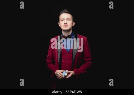 Magicien jeune homme tient des cartes à jouer dans la veste rouge sur fond noir