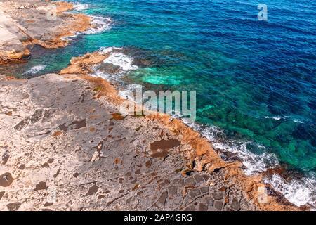 Vue sur la mer bleu Azur avec des vagues qui battent sur la plage et les rochers. Photo aérienne.