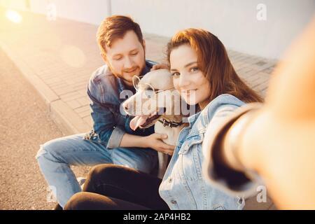 Heureux beau couple s'amuse avec labrador chien Retriever à l'extérieur faire la photo de selfie