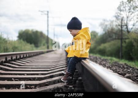Dans yellow jacket Kid sitting on railroad