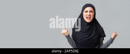 Une jeune fille arabe en colère émotif hurla dans un fond de studio gris Banque D'Images