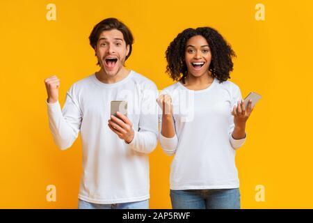 Portrait de jeune homme et de jeune femme surplaisante avec les smartphones Banque D'Images