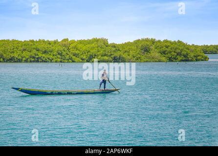 Fadiouth, Sénégal, AFRIQUE - 26 avril 2019 : un homme sénégalais non identifié mandate un canoë en bois typique dans un lagon marin et des poissons. Derrière lui sont Banque D'Images