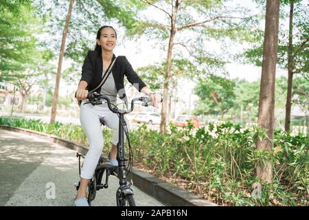 Femme d'affaires souriante qui monte sa moto pliable Banque D'Images