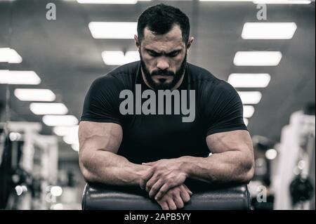 esprit mental sport motivation concept de jeune homme fort avec barbe portant maillot noir concentration détente dans la salle de sport
