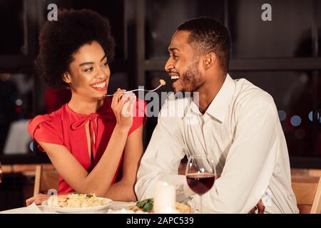 Couple Afro-Américain Se Nourrissage Les Uns Les Autres Dîner Au Restaurant Banque D'Images