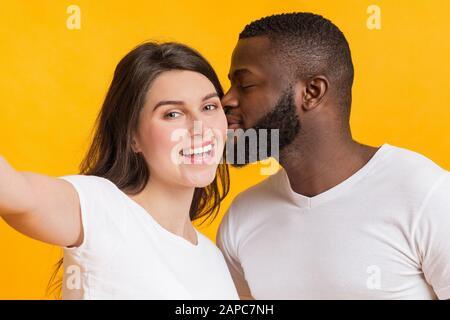 Couple multiracial romantique prenant selfie, affectueux gars noir embrassant sa petite amie Banque D'Images