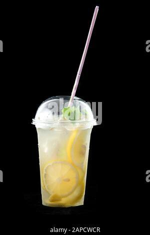 Boisson rafraîchissante froide, limonade ou cocktail de mojito avec citron et menthe. Il y a de la paille dans le verre. Isolé sur fond noir.