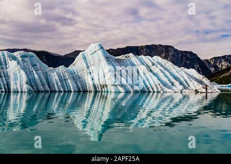 Un paddleboarder debout (SUP) est éclipsé par une énorme glace berg qu'elle paddle à côté de Glacier Bay. Banque D'Images