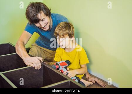 Père et fils montage de meubles. Garçon, il aidait son père à la maison. Concept de famille heureuse Banque D'Images