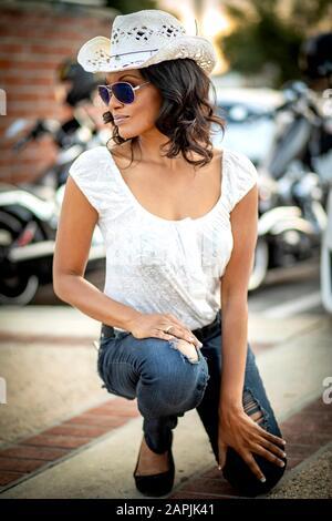 Femme africaine américaine avec lunettes de soleil et chapeau de cow-boy de paille blanche avec moto de rue et mur de brique rouge diffusé en arrière-plan Banque D'Images