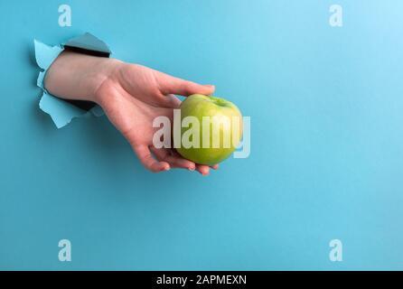 La pomme verte dans la main de la femme est faite d'un trou sur un fond turquoise. Photo horizontale avec espace de copie