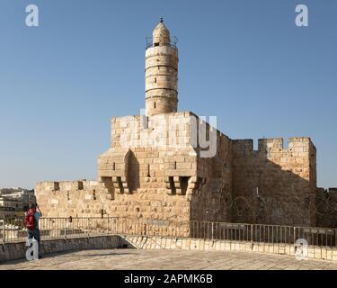 Tourisme photographiant la Tour de David (Citadelle de Jérusalem) avec le minaret de la mosquée dans la vieille ville