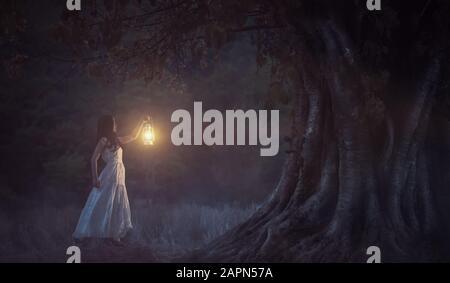 Belle fille en blanc tenant une lanterne dans la forêt d'automne brillant sous les arbres. Banque D'Images