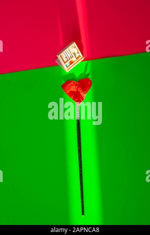Toujours la vie - concept d'amour. Pinceau, coeur et paintbox contre un fond vert et rose néon. Banque D'Images