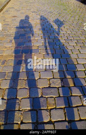 Ombres sombres et allongées de l'homme et de la femme sur un vieux pavé pavé pavé par une journée ensoleillée. Les pierres sont colorées et reflètent les rayons du soleil.