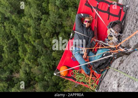 Grimpeur reposant sur le portalisme, l'escalade, le chef Stawamus, le corridor Sea to Sky, Squamish (Colombie-Britannique), Canada Banque D'Images