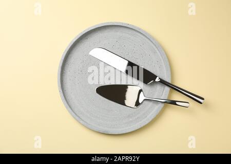 Plateau avec couteau et pelle à pizza sur fond beige, vue de dessus Banque D'Images