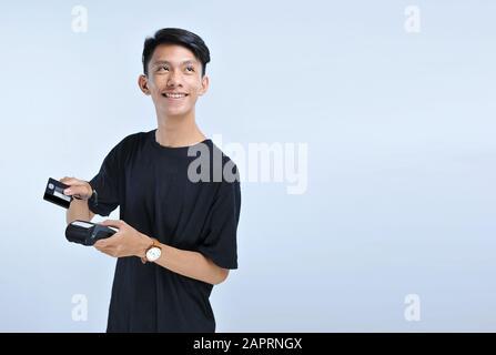 Jeune homme asiatique balayez une carte de crédit / une carte de débit et en regardant l'espace de copie isolé sur le fond gris