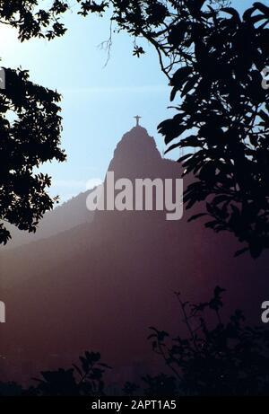 Brésil. Rio de Janeiro. Vue en fin de soirée sur la montagne de Corcovado encadrée de branches d'arbres en silhouette. Banque D'Images