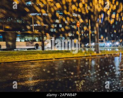 La rue des pluies démoquées vue par le pare-brise de voiture avec le bus public conduite rapidement Banque D'Images