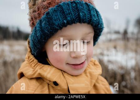 gros plan d'un jeune garçon en regardant vers le bas sourire tout en jouant à l'extérieur