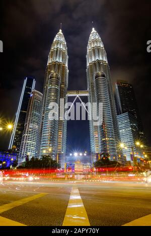 Kuala LUMPUR, MALAISIE - JANJUARY 12, 2020 : gros plan sur la KLCC Petronas Twin Tower la nuit à faible angle par le bord de la route avec sentier léger.