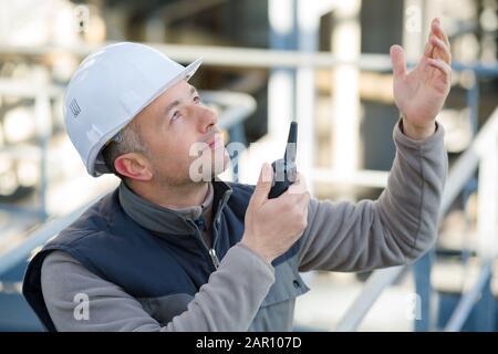 travailleur masculin à l'aide de walkie-talkie à l'extérieur Banque D'Images