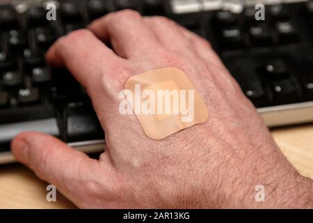 adulte main avec bande adhésive bandage collant plâtre sur le dos travaillant au clavier après un test sanguin pour la maladie Banque D'Images