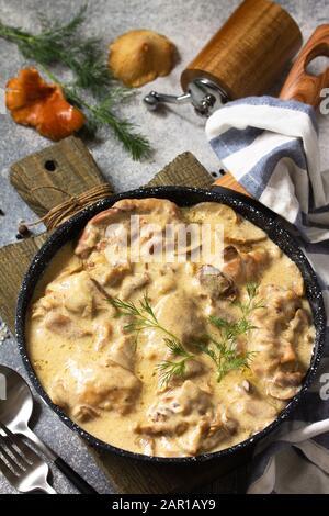 Fricasse - Cuisine Française. Poulet cuit dans une sauce crémeuse aux champignons dans une poêle sur fond de pierre légère.