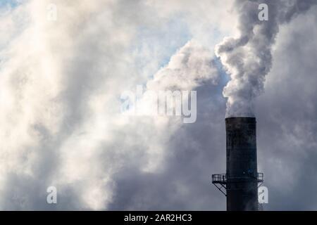 La fumée blanche épaisse et la vapeur s'enlisent d'un fumoir dans une usine textile industrielle, remplissant le ciel de nuages épais lors d'une journée hivernale froide. Banque D'Images