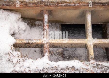 Une tempête sur le côté d'une route de campagne menant à un pont a un dépoussiérage de neige en hiver. La grille métallique sur le dessus est roulante.