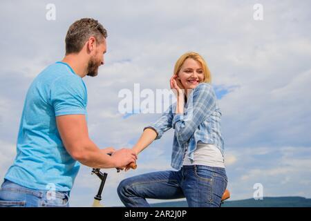 concept de connaissance asual. Homme avec barbe et fille blonde timide à la première date. La femme se sent timide en compagnie avec macho attrayant. Le couple se réunit pour se détendre ensemble. Romance ou date de vélo. Banque D'Images