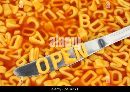 Épettis de l'alphabet ouvert avec des lettres aléatoires dans le fond de sauce tomate Banque D'Images