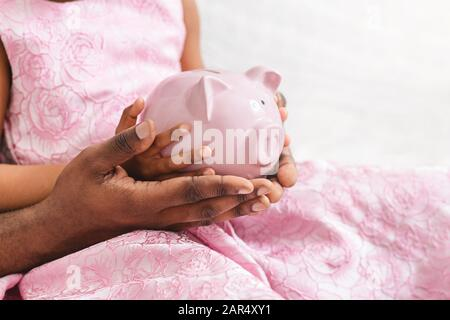 Gros plan sur le père noir et la fille tenant la banque de porc