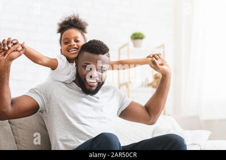 Beau père de famille noir et fille posant à la maison Banque D'Images
