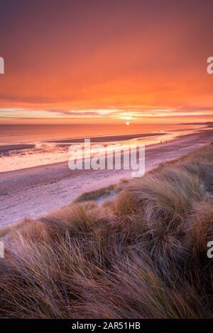 Un lever de soleil orange vif et lumineux depuis les dunes de sable au-dessus de la plage de la baie de Druridge et de la mer du Nord sur la côte de Northumberland en hiver.