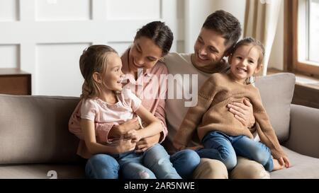 Une jeune famille affectueuse avec des enfants se détendre dans le salon Banque D'Images