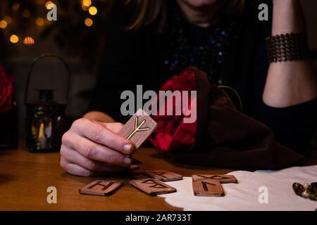 Fortune en racontant les runes. La sorcière de femme mûre présente les runes. Elle semble préoccupée et anxieuse. Banque D'Images
