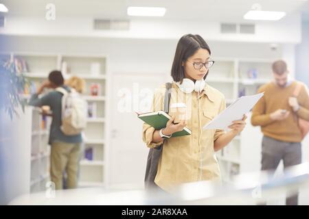 Taille haut portrait de la jeune fille asiatique d'adolescence lire rapport tout en se tenant à la bibliothèque de l'université, espace de copie Banque D'Images